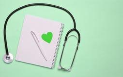 Notizblock mit Stift, dekoratives Herz, Stethoskop auf rosa Pastellb stockfotografie