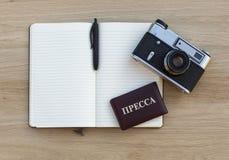 Notizblock mit Stift, Filmkamera und Russe drücken Identifikation, die auf einem Holztisch liegt Lizenzfreie Stockbilder