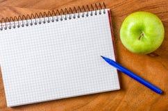 Notizblock mit Stift und Apfel Stockbilder