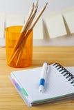 Notizblock mit Stiftbehälter mit Bleistiften liegen auf einem Holztisch Auf der Wand nahe der Tabelle klebte Papier für Anmerkung Stockbilder