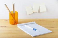 Notizblock mit Stiftbehälter mit Bleistiften liegen auf einem Holztisch Weißer Hintergrund Lizenzfreie Stockbilder