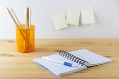 Notizblock mit Stiftbehälter mit Bleistiften liegen auf einem Holztisch Weißer Hintergrund Stockbilder