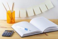 Notizblock mit Stiftbehälter mit Bleistiften, Taschenrechner sind auf einem Holztisch Auf der Wand nahe der Tabelle klebte Papier Lizenzfreie Stockfotografie