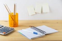 Notizblock mit Stiftbehälter mit Bleistiften, Taschenrechner sind auf einem Holztisch Auf der Wand nahe der Tabelle klebte Papier Lizenzfreies Stockfoto