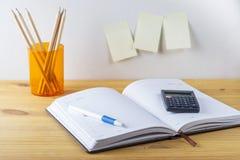 Notizblock mit Stiftbehälter mit Bleistiften, Taschenrechner sind auf einem Holztisch Auf der Wand nahe der Tabelle klebte Papier Stockbild