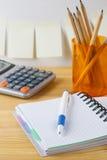 Notizblock mit Stiftbehälter mit Bleistiften, Taschenrechner sind auf einem Holztisch Auf der Wand nahe der Tabelle klebte Papier Lizenzfreie Stockfotos