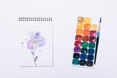 Notizblock mit Zeichnung einer Blume und des Aquarells auf weißer Tabelle Stockbild
