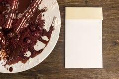 Notizblock, Moosbeerkuchen, heiße Schokolade auf dem Kuchen, Puderzucker Stockbilder