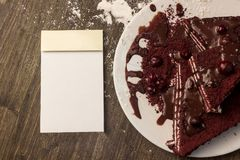 Notizblock, Moosbeerkuchen, heiße Schokolade auf dem Kuchen, pulverisiertes sug Stockbild
