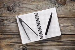 Notizblock, Stift, Kompassse auf einem Holztisch Beschneidungspfad eingeschlossen lizenzfreie stockfotografie