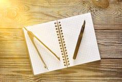 Notizblock, Stift, Kompassse auf einem Holztisch Beschneidungspfad eingeschlossen stockbild