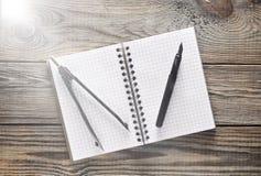 Notizblock, Stift, Kompassse auf einem Holztisch Beschneidungspfad eingeschlossen stockfoto