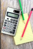 Notizblock, Taschenrechner und bunte Bleistifte Stockbild