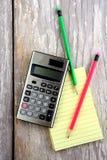 Notizblock, Taschenrechner und bunte Bleistifte Stockfotos