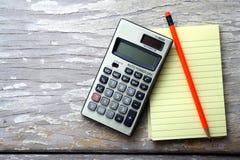 Notizblock, Taschenrechner und ein bunter Bleistift Stockfotos