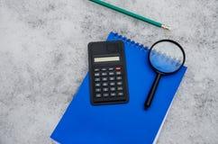Notizblock, Taschenrechner, Vergrößerungsglas, Bleistift gesetzt auf einen Hintergrund des Schnees stockbilder