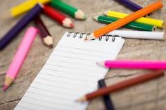 Notizblock und bunte Bleistifte auf Holztisch Stockfotografie
