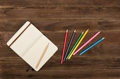 Notizblock und farbige Bleistifte auf einem Holztisch Stockfotografie