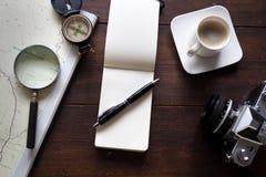 Notizblock und Kaffee mit Karte und Kompass auf Schreibtisch Stockfotos
