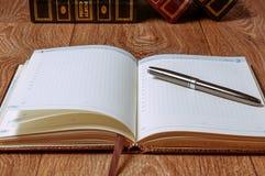 Notizblock und Stift auf Holztisch Stockfotos