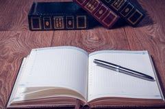 Notizblock und Stift auf Holztisch Stockbild