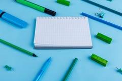 Notizblock und verschiedene Bleistifte, Markierungen und stationeryare gesetzt auf einen blauen Hintergrund Stockfotografie