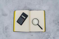 Notizblock, Vergrößerungsglas und Taschenrechner stockbilder