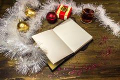 Notizblock-, Weihnachtsbälle, weiße Girlande, Tee und Geschenk Lizenzfreie Stockbilder