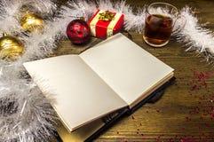 Notizblock-, Weihnachtsbälle, weiße Girlande, Tee und Geschenk Lizenzfreies Stockfoto