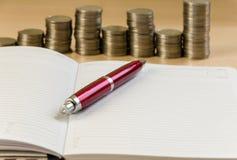 Notizblockstift und -münzen Stockfoto