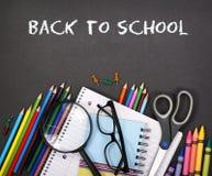 Notizbuch, Übungsbuch, Scheren und Bleistifte auf schwarzem Brett Lizenzfreie Stockbilder