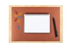 Notizbuch auf dem braunen strukturierten Papier, das einen Rahmen nachahmt Stockbilder