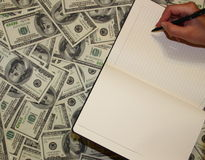 Notizbuch auf dem Hintergrund des Geldes Stockbilder