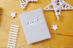 Notizbuch auf einem hölzernen Hintergrund mit einem Dekor von Weiß spielt Ebenenlage, Draufsichtfotomodell die Hauptrolle Lizenzfreie Stockfotografie