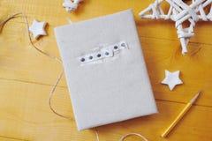 Notizbuch auf einem hölzernen Hintergrund mit einem Dekor von Weiß spielt Ebenenlage, Draufsichtfotomodell die Hauptrolle Stockfoto