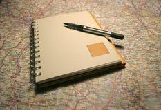 Notizbuch auf einer Karte Lizenzfreies Stockbild