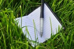 Notizbuch auf Gras Stockfotos