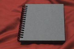 Notizbuch auf rotem Gewebe, Notizbuch ist, Weinlesenotizbuchabdeckung grau Stockbild