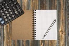 Notizbuch, ballpen und Taschenrechner auf hölzernem Schreibtisch Stockfotos