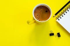 Notizbuch, Bleistift und Kaffeetasse auf gelbem Hintergrund lizenzfreie stockbilder