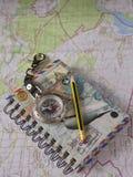 Notizbuch, Bleistift und Kompass, die auf einer topographischen Karte liegen Stockfotografie