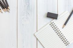 Notizbuch, Bleistift und Radiergummi auf Holztisch, Draufsicht, Konzept des Arbeitsplatzes, Büroartikel, Hintergrund Lizenzfreies Stockfoto
