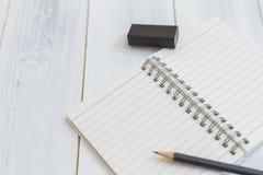 Notizbuch, Bleistift und Radiergummi auf Holztisch, Großaufnahme, Konzept des Arbeitsplatzes, Büroartikel, backgr Stockfoto