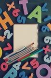Notizbuch, Bleistifte, Filzstifte, Bürste gegen Farbbuchstaben und Zahlen Lizenzfreies Stockbild
