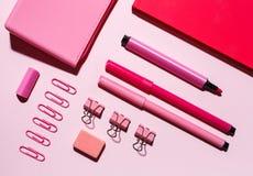 Notizbuch, Bleistiftkastenlüge auf dem rosa Hintergrund stockfotos