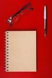 Notizbuch, das auf einem Rot mit Stift liegt Lizenzfreies Stockfoto