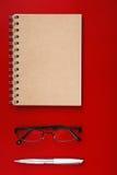 Notizbuch, das auf einem Rot mit Stift liegt Stockbild