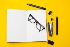 Notizbuch für Anmerkungen und Briefpapier auf einem gelben Hintergrund Educat Stockfoto