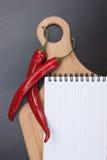 Notizbuch für das Kochen von Rezepten und von Pfeffern des roten Paprikas Stockbilder