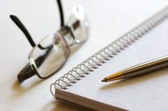 Notizbuch, Feder und Brillen Lizenzfreie Stockbilder